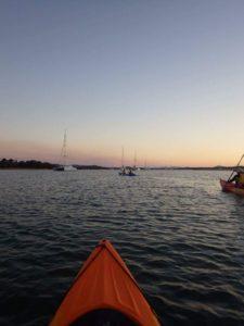 Kayakfahren während des Sonnenuntergangs